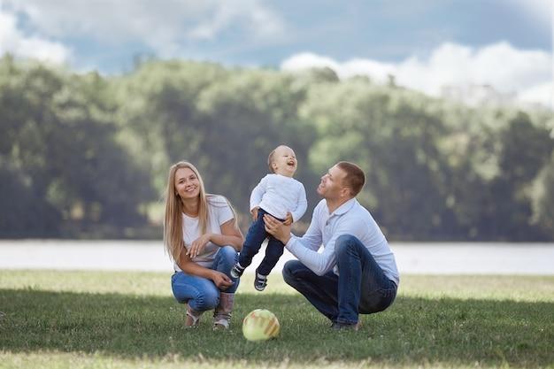 Ouders en hun zoontje spelen met de bal op het gazon. het concept van actieve recreatie