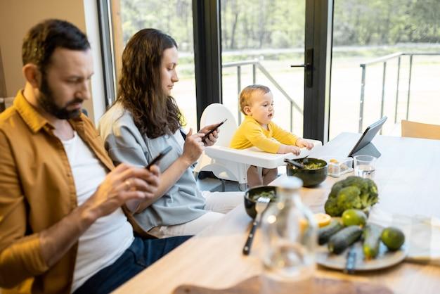 Ouders en hun zoontje van één jaar zitten op mobiele apparaten tijdens de lunch thuis
