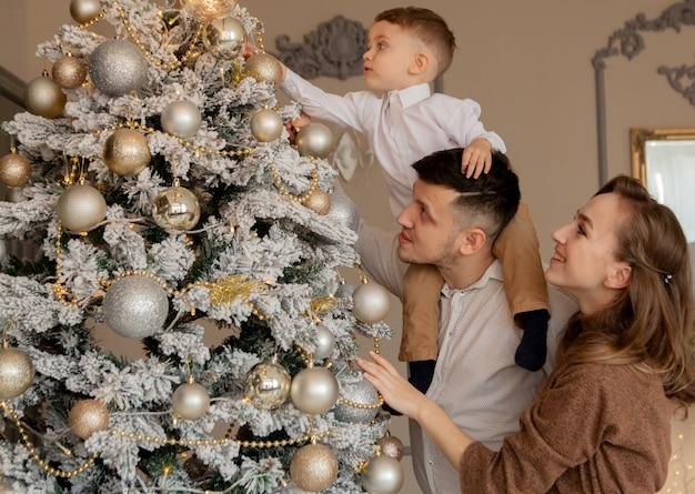 Ouders en hun zoontje versieren kerstboom met speelgoed en slingers.