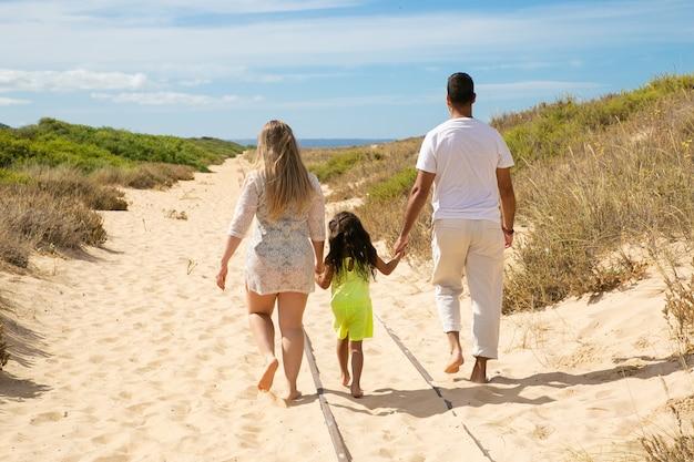 Ouders en kind dragen zomerkleding, wandelen langs zandpad naar zee, meisje hand in hand van de ouders