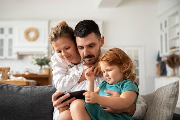 Ouders en kind met medium shot op apparaat