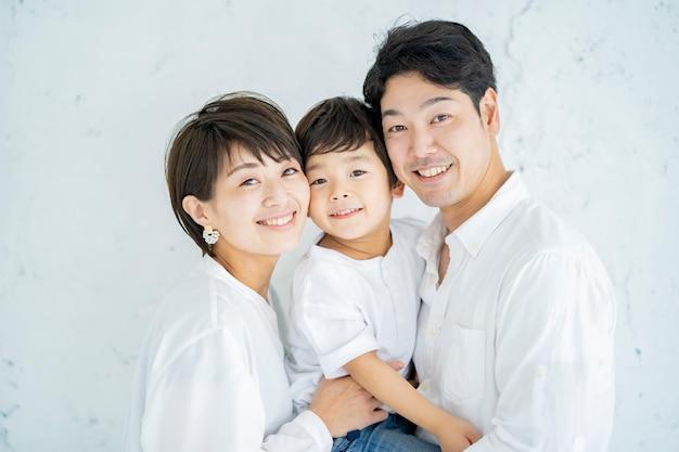 Ouders en kind opgesteld met een glimlach en een gestructureerde witte achtergrond