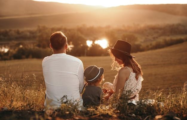 Ouders en kind rusten tijdens picknick bij zonsondergang