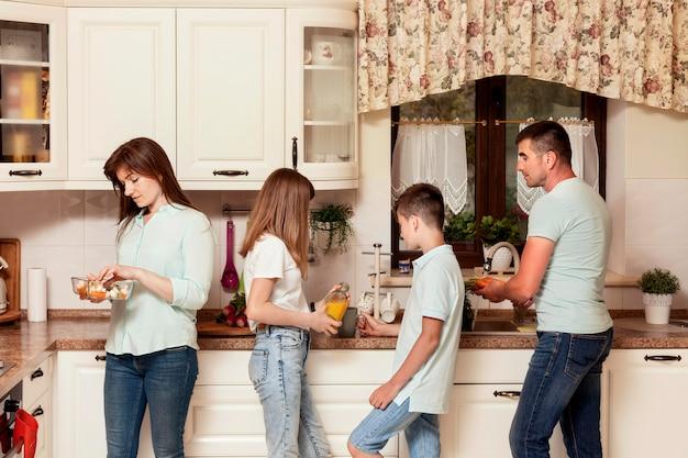 Ouders en kinderen bereiden voedsel in de keuken voor het diner
