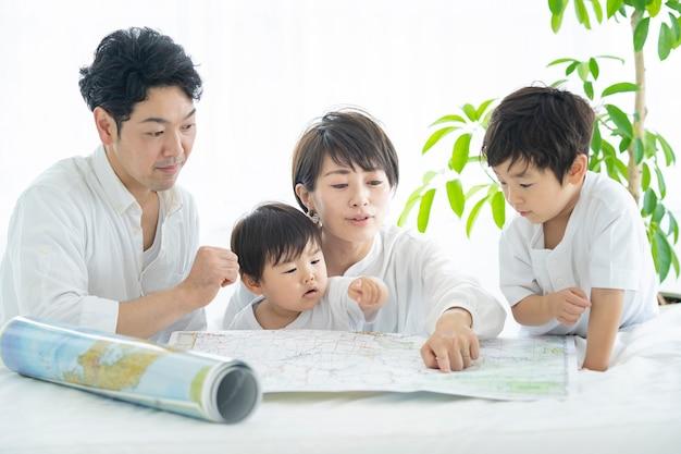 Ouders en kinderen die met plezier studeren met kaarten ã£âƒâ» ouders en kinderen die reizen plannen met kaarten