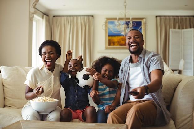 Ouders en kinderen hebben plezier tijdens het televisiekijken in de woonkamer