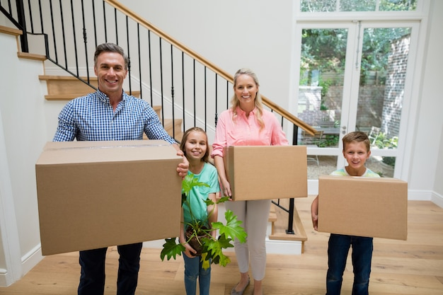 Ouders en kinderen houden van kartonnen dozen in de woonkamer thuis