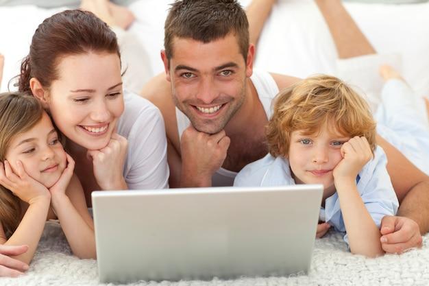 Ouders en kinderen in bed met behulp van een laptop