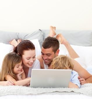 Ouders en kinderen in bed spelen met een laptop