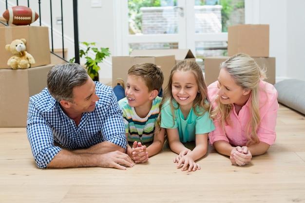 Ouders en kinderen liggend op de vloer in de woonkamer
