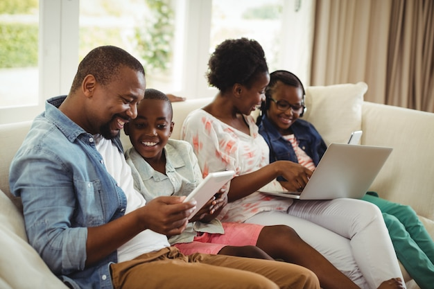 Ouders en kinderen met behulp van laptop en digitale tablet op sofa