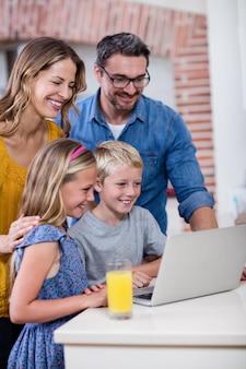 Ouders en kinderen met behulp van laptop in de keuken