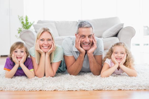 Ouders en kinderen met hoofd in handen liggend op tapijt