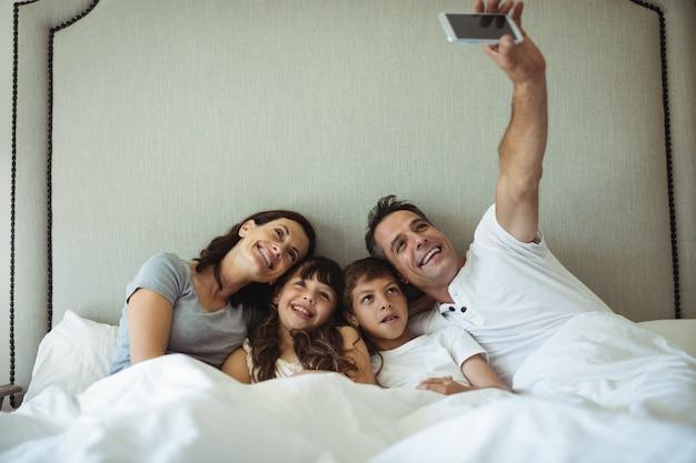 Ouders en kinderen nemen een selfie op bed