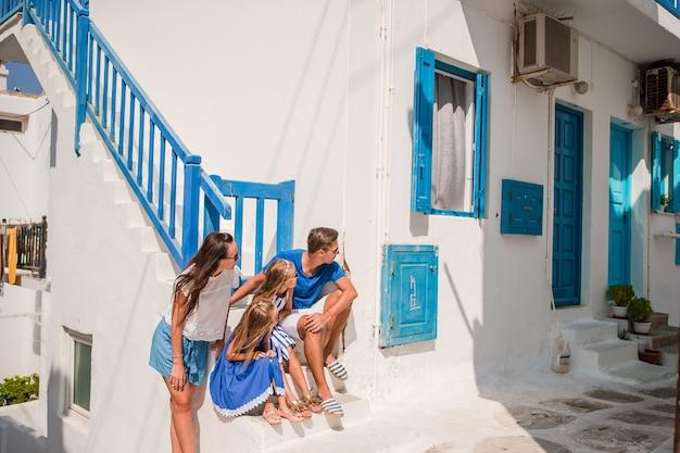 Ouders en kinderen op straat van typisch grieks traditioneel dorp met witte muren