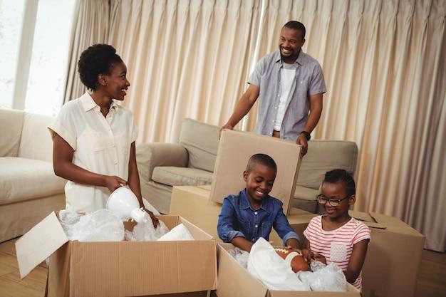 Ouders en kinderen openen kartonnen dozen in de woonkamer