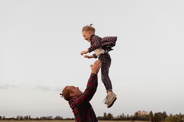 Ouders en kinderen. tijdens een gezinswandeling gooit de vader het kind overeind