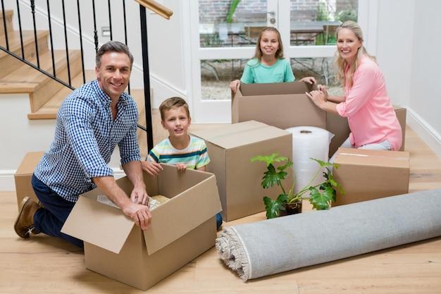 Ouders en kinderen uitpakken kartonnen dozen in de woonkamer