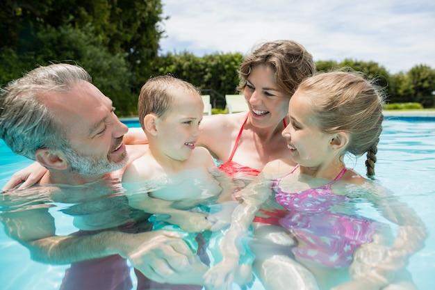 Ouders en kinderen vermaken zich bij het zwembad