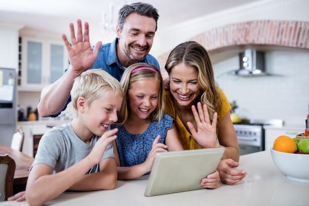 Ouders en kinderen zwaaiende handen tijdens het gebruik van digitale tablet voor videochat