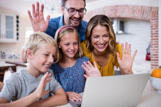 Ouders en kinderen zwaaiende handen tijdens het gebruik van laptop voor videochat