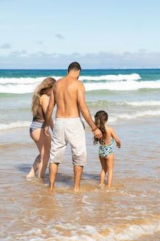 Ouders en meisje die in zwemkleding enkel diep in oceaangolven lopen