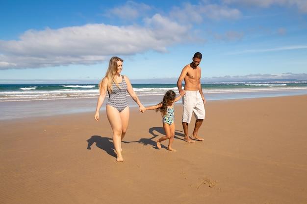 Ouders en meisje dragen zwemkleding, lopen op het gouden zand van de zee
