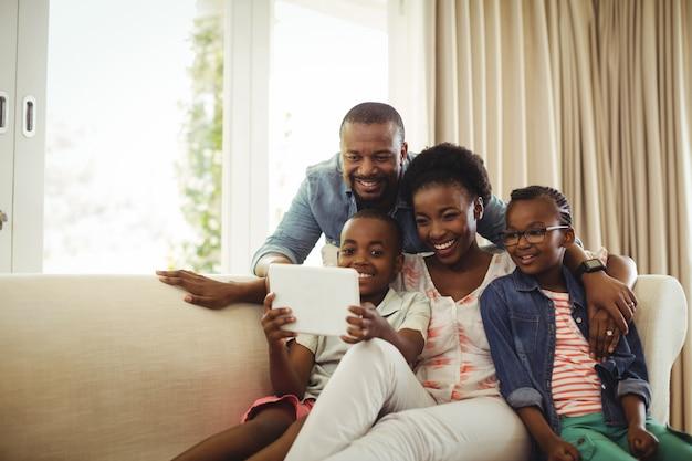 Ouders en zoon die digitale tablet op bank in woonkamer gebruiken