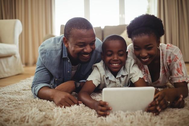 Ouders en zoon met behulp van digitale tablet liggend op een tapijt
