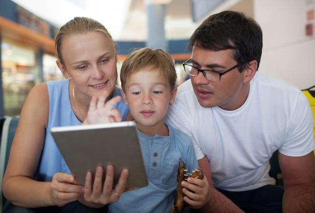 Ouders en zoon met tablet-pc op de luchthaven