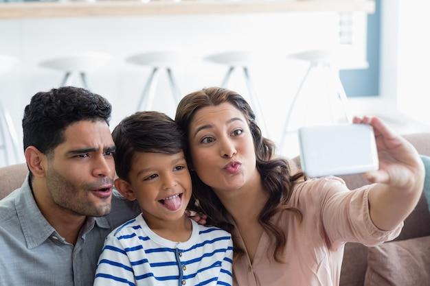 Ouders en zoon nemen een selfie van mobiele telefoon in de woonkamer