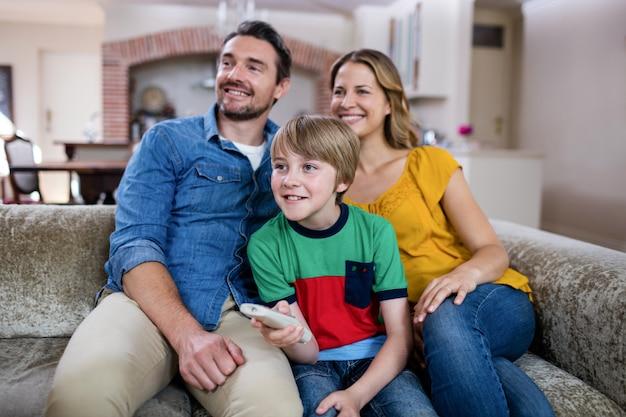 Ouders en zoon televisie kijken in de woonkamer