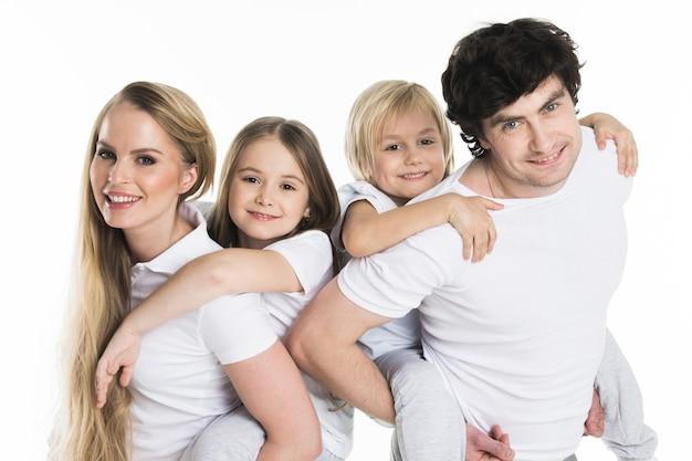 Ouders geven kinderen op de rug rit studio geïsoleerd op wit oppervlak