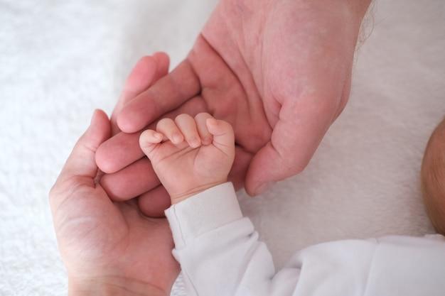 Ouders houden de hand van hun pasgeboren baby in hun armen, handen van dichtbij