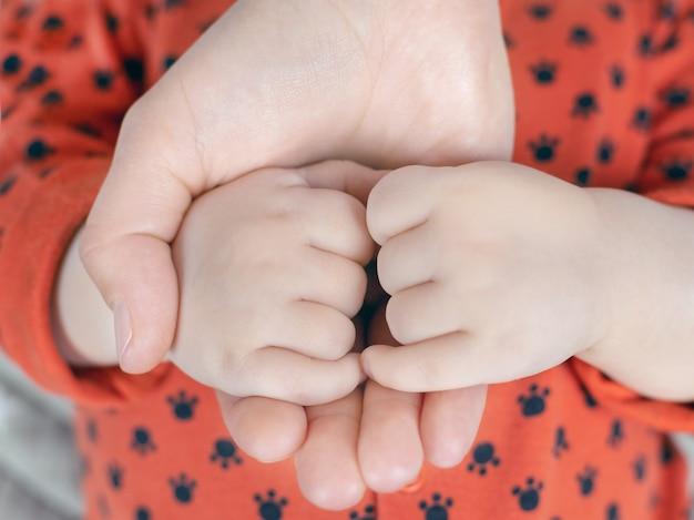 Ouders houden de schattige kleine handjes van hun baby vast, concept van de zorg voor gezinsliefde en geluk, close-up
