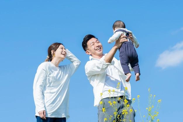 Ouders houden hun baby hoog onder de blauwe lucht