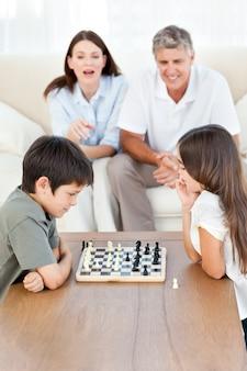 Ouders kijken hun kinderen aan het schaken