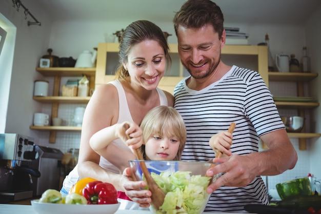 Ouders kijken naar hun dochter die de salade mengt
