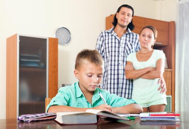 Ouders kijken naar hun zoon die huiswerk maakt