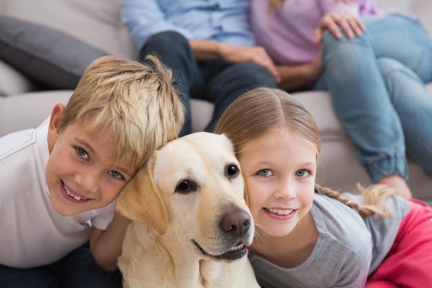 Ouders kijken naar kinderen op tapijt met labrador