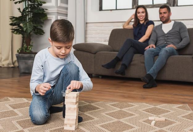 Ouders kijken naar zoon die jenga speelt