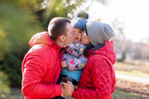 Ouders kussen het kind in de herfstpark