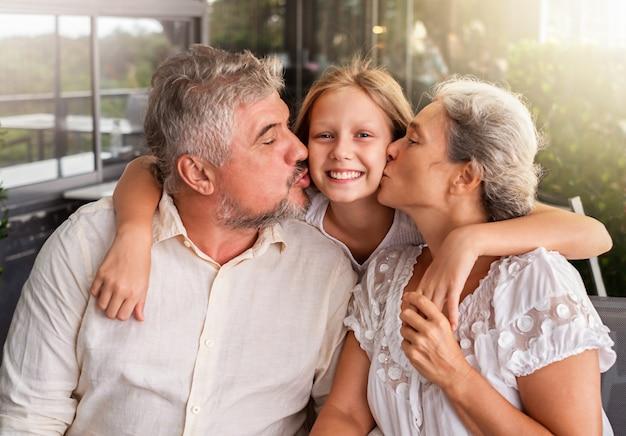 Ouders kussen hun dochter. de man en de vrouw omhelzen en kussen hun kind