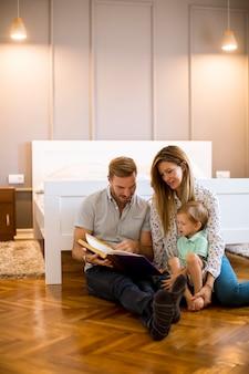 Ouders lezen boek aan kleine jongen en hebben plezier op de vloer
