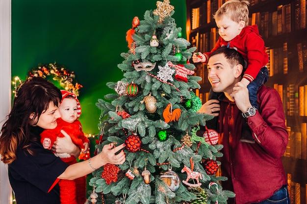 Ouders maken zich klaar kerstboom met hun kleine jongens