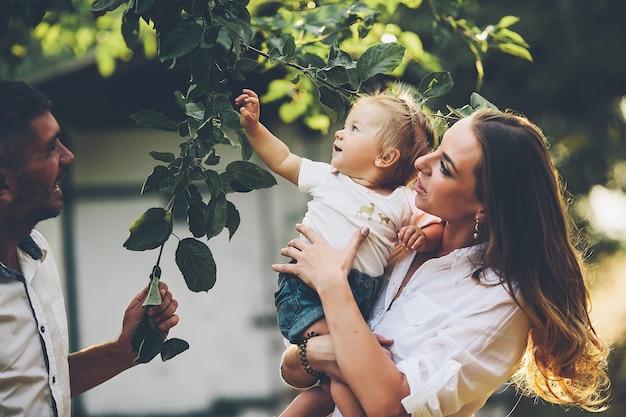 Ouders met baby genieten van picknick op een boerderij met appel- en kersenbomen.