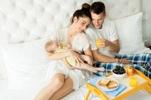 Ouders met baby ontbijten in bed