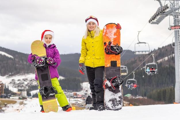Ouders met dochter die wintervakantie vieren. familie in kerstmuts en snowboard in winterresort