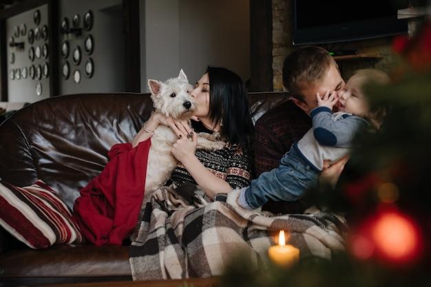 Ouders met een baby bij kerstmis en een hond zit op de bank