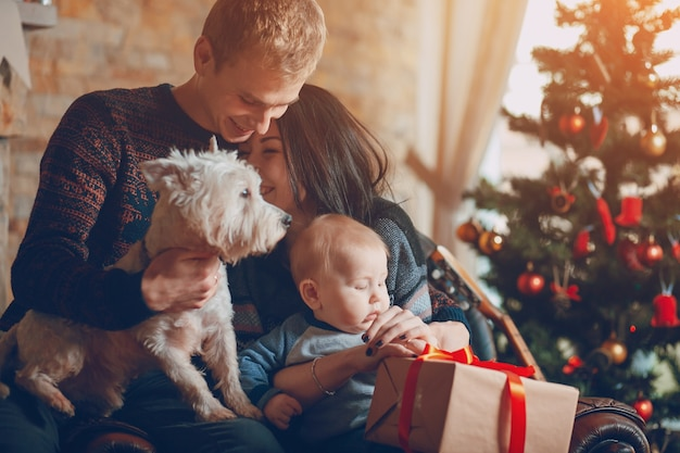 Ouders met een hond en een baby met een kerst boom achtergrond